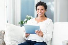 使用在沙发的愉快的妇女画象片剂 免版税库存照片