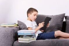 使用在沙发的男孩一台片剂个人计算机 在白色后面的演播室画象 免版税图库摄影