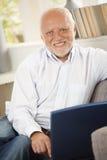 使用在沙发的老人纵向计算机 免版税图库摄影