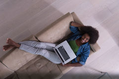 使用在沙发顶视图的非裔美国人的妇女膝上型计算机 库存照片