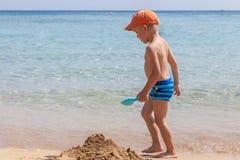 使用在沙子和波浪的男孩在海滩 免版税库存照片