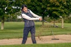 使用在沙子地堡外面的女子高尔夫球运动员 免版税库存图片
