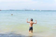 使用在沙子海滩的年轻亚裔泰国男孩 库存图片