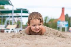 使用在沙子的微笑的小男孩 正面人的情感,感觉, 库存图片