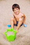使用在沙子的微笑的男孩 免版税库存图片