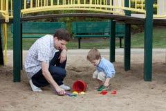 使用在沙子的操场的父亲和儿子 图库摄影