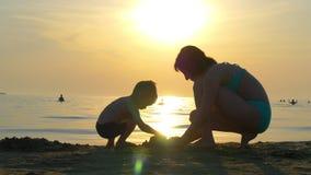 使用在沙子的海滩的一个愉快的母亲和孩子的剪影 妈妈和孩子修造沙子城堡反对 影视素材