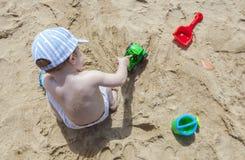 使用在沙子的男婴在与玩具反向铲的海滩,浇灌 免版税库存图片