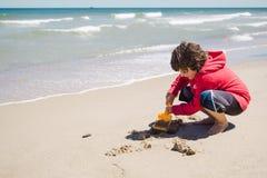 使用在沙子的男孩 免版税图库摄影