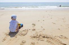 使用在沙子的男婴,当其他孩子飞溅此外时 免版税库存图片