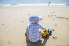 使用在沙子的男婴,当他的姐妹在海滩s旁边时跑 免版税库存图片