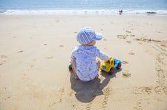 使用在沙子的男婴,当他的姐妹在海滩s旁边时跑 免版税图库摄影