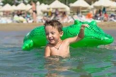 使用在沙子的画象微笑的小男婴在se附近 免版税图库摄影