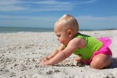 使用在沙子的逗人喜爱的女婴在海滩 库存图片