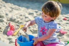 使用在沙盒沙子土墩的操场的小迷人的女孩婴孩在有铁锹和犁耙的桶 免版税库存照片