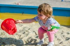 使用在沙盒沙子土墩的操场的小迷人的女孩婴孩在有铁锹和犁耙的桶 免版税库存图片