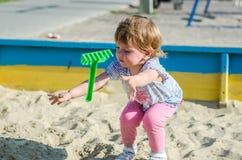 使用在沙盒沙子土墩的操场的小迷人的女孩婴孩在有铁锹和犁耙的桶 免版税图库摄影