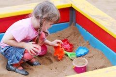 使用在沙盒的美丽的逗人喜爱的小女孩 免版税库存照片