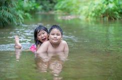 使用在河的兄弟和姐妹在夏天 免版税库存图片