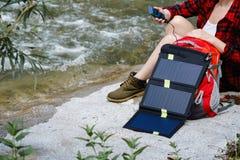 使用在河的妇女智能手机 使用太阳电池板的充电 免版税图库摄影