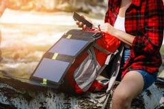 使用在河的妇女智能手机 使用太阳电池板的充电 免版税库存图片