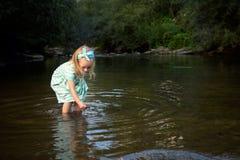 使用在河,探险概念的可爱的白肤金发的女孩 免版税图库摄影