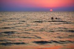 使用在波浪的孩子剪影在日落 免版税库存照片
