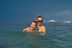 使用在波浪的微笑的愉快的母亲和儿子在海自白天 放松由海的愉快的家庭 夏天、春天和w 库存照片