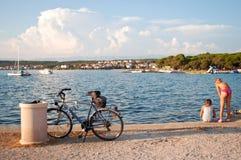 使用在海岸的两个女孩在自行车附近 免版税图库摄影