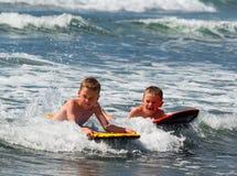 使用在海浪的两个男孩 免版税库存照片