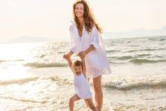 使用在海海滩的母亲和女儿在希腊 免版税图库摄影