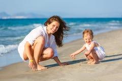 使用在海海滩的母亲和女儿在希腊 免版税库存照片