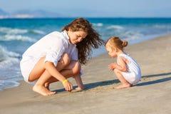 使用在海海滩的母亲和女儿在希腊 免版税库存图片