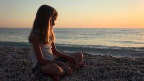 使用在海滩在日落,在海水4K的女孩投掷的小卵石的孩子 股票录像