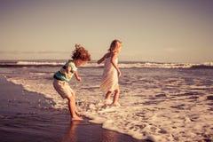 使用在海滩的两个愉快的孩子在天时间 库存照片