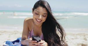 使用在海滩的俏丽的女孩电话 影视素材