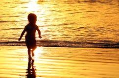 使用在海滩的孩子在巴厘岛,在金黄日落期间的印度尼西亚 海洋喜欢金子 免版税库存照片