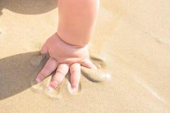 使用在海滩的小小孩婴孩在海 在沙子的小手 晴朗日的夏天 假期童年育儿慈善 免版税库存照片