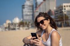 使用在海滩的年轻逗人喜爱的妇女智能手机 城市地平线在背景中 库存照片