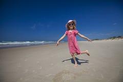 使用在海滩的愉快的女孩 免版税库存图片