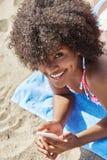 使用在海滩的愉快的美国黑人的妇女机动性 图库摄影