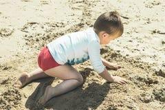 使用在海滩的沙子的孩子的特写镜头 免版税库存照片