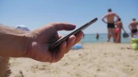 使用在海滩的流动智能手机关闭人 有黑屏幕的,发短信,视频通话,沿海岸区,假日电话 股票视频