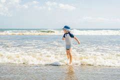 使用在海滩的男孩在水中 免版税库存图片
