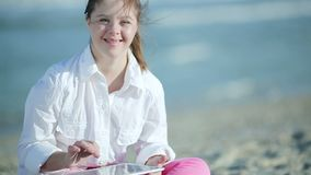 使用在海滩的触摸屏幕片剂的唐氏综合症女孩 影视素材
