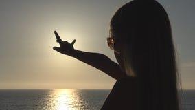 使用在海滩,在日落,在太阳光芒的女孩手,射线的孩子的儿童剪影 图库摄影