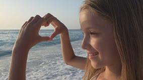 使用在海滩,孩子观看的海波浪,女孩的孩子做心形爱标志 免版税库存图片