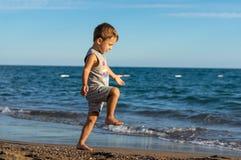 使用在海的微笑的小男婴 正面人的情感,感觉 免版税库存照片