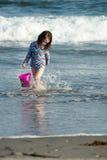 使用在海边的年轻逗人喜爱的小女孩运载一个红色桶在海浪的边缘在一个沙滩的在夏天 免版税库存照片