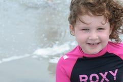 使用在海边的年轻逗人喜爱的小女孩遇到在一个沙滩的海浪在夏天阳光下 免版税库存图片